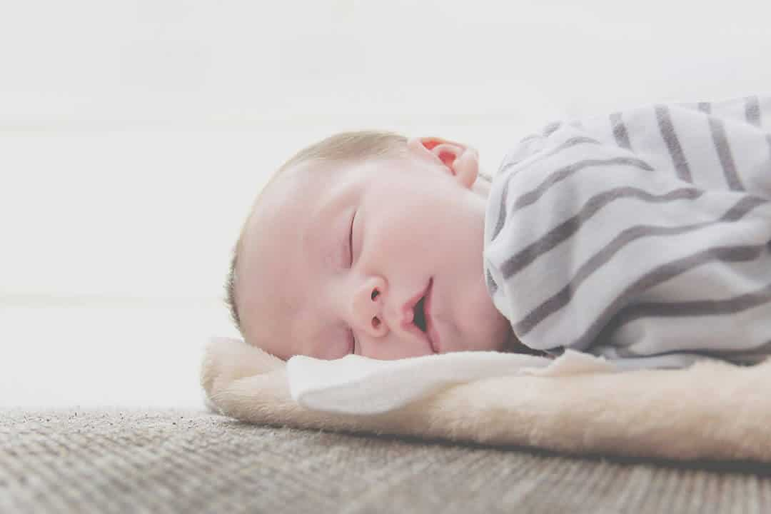 A newborn baby is sleeping well on his bed