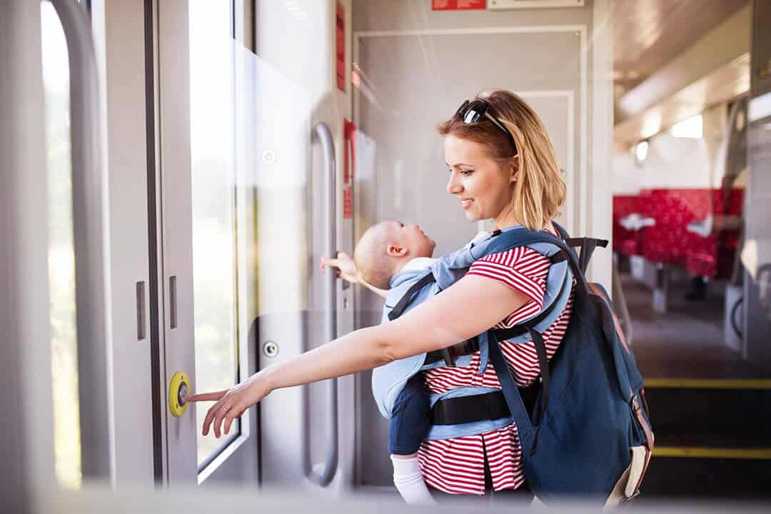 mom holding a baby and carrying a diaper backpack